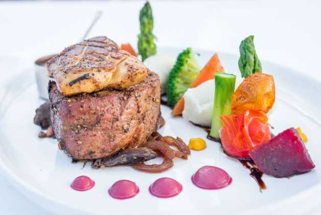 Tournedos of Rossini\n8 oz beef fillet, mashed potatoes, foie gras crusted, caramel onion, roasted vegetables, madeira sauce